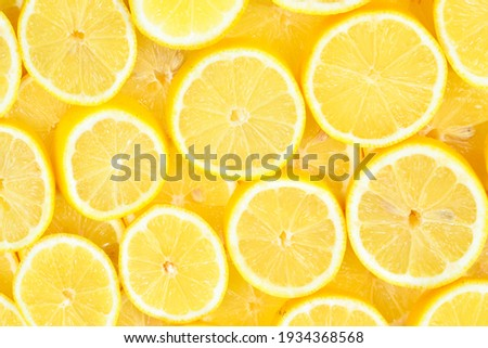 A slices of fresh juicy yellow lemons.  Texture background, pattern. Royalty-Free Stock Photo #1934368568