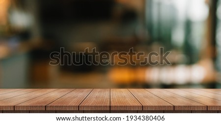 Empty wooden table top with lights bokeh on blur restaurant background. Royalty-Free Stock Photo #1934380406