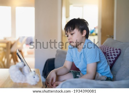 Kid having fun watching cartoon or play game on tablet, School boy using digital pad searching the ideas on internet for his homework,Home schooling, Home learning or E-learning online education