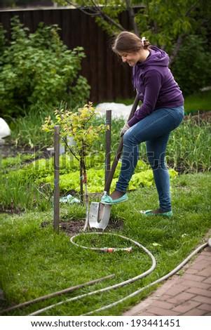 Beautiful woman digging bed with shovel at garden #193441451