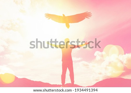 Man raise hand up on top of mountain and sunset sky with eagle birds fly abstract background. Copy space freedom travel adventure and business victory concept. Vintage tone filter effect color style. Royalty-Free Stock Photo #1934491394