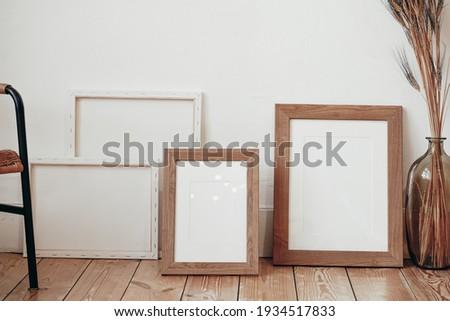 Square wooden frame mockup on vintage floor. Modern vase with dry Lagurus ovatus grass. White wall background. Scandinavian interior.