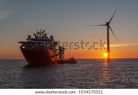 Service operational vessel, with crew transfer vessel alongside and sun setting on wind turbine Royalty-Free Stock Photo #1934570351