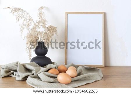 Spring, Easter still life. Empty picture frame mockups. Linen tablecloth, hen eggs. Reed grasses in a ceramic jug. Farmhouse, Scandinavian interior.