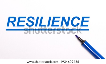 On a light background, an open blue felt-tip pen and the text RESILIENCE