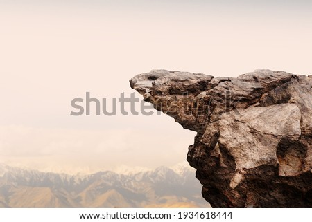 Cliff stone with mountain on clouds sky. Royalty-Free Stock Photo #1934618444