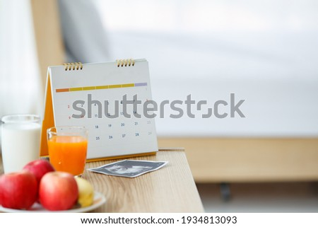 Photos of calendar, a glass of orange juice and milk with a white ceramic plate of apples and banana, and ultrasound scan picture on a wooden table. Selective focus on a calendar.