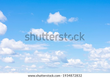 Lots of cumulus clouds far on horizon on blue daylight sky as natural background Royalty-Free Stock Photo #1934872832