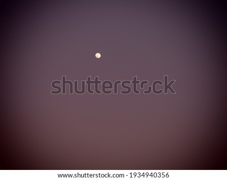 Moon in the night purple sky. White point in the sky. Dark vignetting around the edges of the image