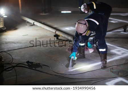 Male worker test spaying white contrast magnetic field test white contrast carbon bottom plate of storage tank oil background  of magnetic field test Royalty-Free Stock Photo #1934990456