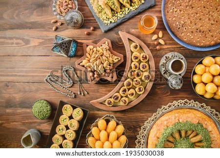 Arabic Cuisine: Middle Eastern desserts. Delicious collection of Ramadan traditional desserts. Served with tasty nuts, Arabic coffee, honey syrup and sugar syrup .Top view with close up. Royalty-Free Stock Photo #1935030038