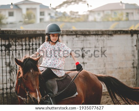 Asian shool kid girl with horse ,riding or practicing horse ridding at horse ranch