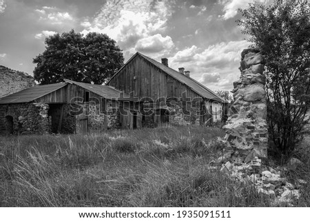 Old destroyed wooden house. Black and white photo Royalty-Free Stock Photo #1935091511