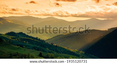mountainous countryside scenery at sunset. dramatic sky above the distant valley. green fields and trees on the hill. beautiful nature scenery of carpathians Royalty-Free Stock Photo #1935120731