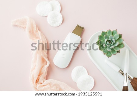 Ultrasonic Skin Scrubber Exfoliating Wand on pink background with bathroom items