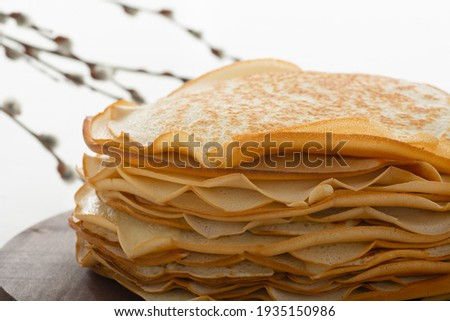 A stack of pancakes on a wooden stand. Beautiful light blurred background and the top of the pancakes. Openwork edges of pancakes beautifully decorate the picture. Space for text. Масленица