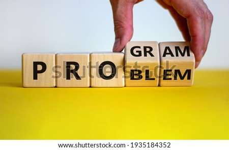 Solving a problem and making program symbol. Businessman turns wooden cubes and changes the word 'problem' to 'program'. Beautiful white background. Business, problem to program concept. Copy space.