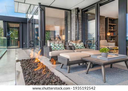 Exterior deck with large open gas fire Royalty-Free Stock Photo #1935192542