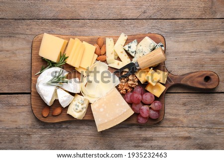 Cheese plate with grapes and nuts on wooden table, top view Royalty-Free Stock Photo #1935232463