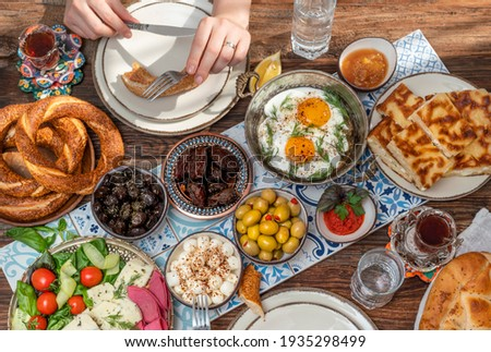 Delicious rich Traditional Turkish breakfast include tomatoes, cucumbers, cheese, butter, eggs, honey, bread, bagels, olives and tea cups. Ramadan Suhoor aka Sahur (morning meal before fasting).  Royalty-Free Stock Photo #1935298499