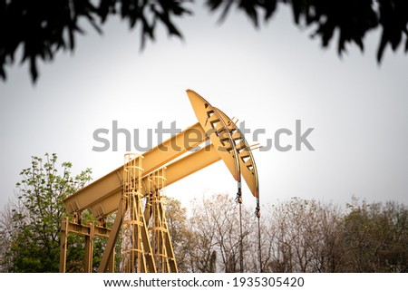 Beam pump or Donkey pump, operating for crude oil enhancing in petroleum industrial, photo with shadow of tree's leaf above as border frame. Oil industrial operation and equipment object.