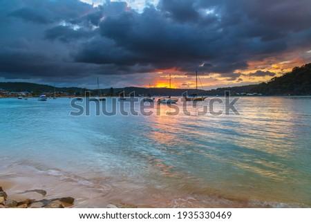 Rain clouds and sunrise at Ettalong Beach on the Central Coast, NSW, Australia. Royalty-Free Stock Photo #1935330469