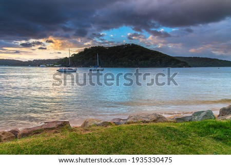 Rain clouds and sunrise at Ettalong Beach on the Central Coast, NSW, Australia. Royalty-Free Stock Photo #1935330475