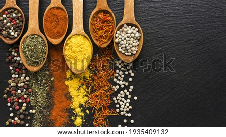 close up of a spoon herbs and spices  in a spoon in wooden black desk natural food pepper healthy salt red chili close up paprika new picture ingredients seeds powder kitchen herbs spicy wood cooking
