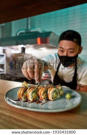 Professional sushi chef wearing protective mask and gloves decorating sushi rolls preparing to be served on plate at commercial kitchen. Food photography, Asian cuisine, restaurant service concept