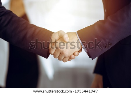 Unknown businesspeople are shaking their hands after signing a contract, while standing together in a sunny modern office, close-up. Business communication concept Royalty-Free Stock Photo #1935441949