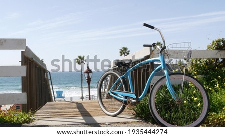 Blue bicycle, cruiser bike by ocean beach, pacific coast, Oceanside California USA. Summertime vacations sea shore. Vintage cycle by wooden stairs, stairway or staircase. Tropical palms and lifeguard Royalty-Free Stock Photo #1935444274