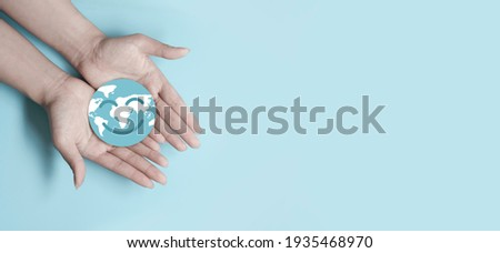Hands holding smile earth paper cut, save planet, earth day, sustainable living, ecology environment, climate emergency action, world environment day concept, illustration for global warming content Royalty-Free Stock Photo #1935468970