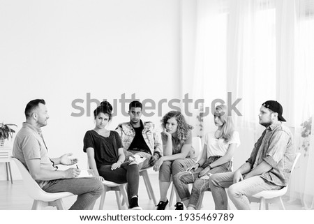 Black and white photo of group of teenagers during psychotherapy with professional counselor , copy space on empty white wall