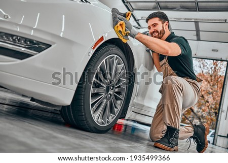 Car detailing series. Worker cleaning white car. Selective focus. Low angle view. Royalty-Free Stock Photo #1935499366