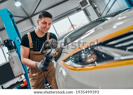 Auto mechanic worker polishing car at automobile repair and renew service station shop by power buffer machine. Selective focus. Close up view. Royalty-Free Stock Photo #1935499393