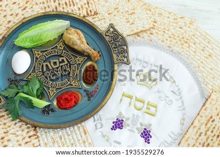 Pesah celebration concept (jewish Passover holiday). Traditional pesah text in hebrew: Passover, horseradish, celery, egg, bone, maror, sweet dates jam