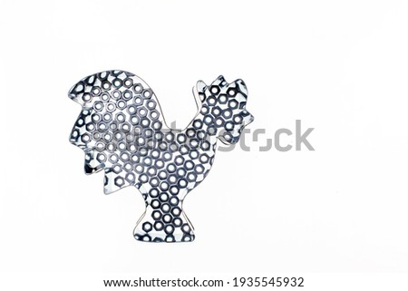 outline of a rooster made of shiny metal and nuts on a white background