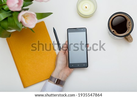 Mockup image of cell phone in female hand. Design creative work space top view, template