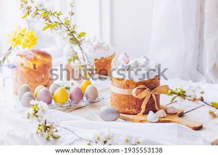 Traditional ukrainian easter cake with white swiss meringue. New cruffin cake trend 2021. Spring cherry blossom and colorful painted eggs. Person decorates cake with hand. Free copy space. Royalty-Free Stock Photo #1935553138