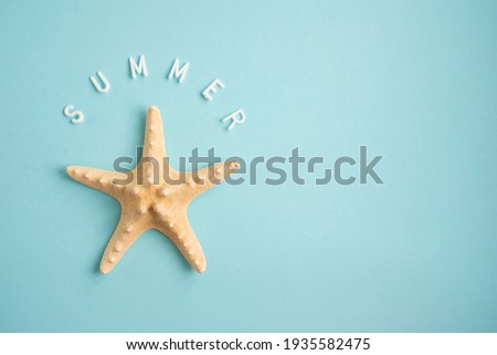Starfish on a blue background and the word Summer. Vacation concept.  Royalty-Free Stock Photo #1935582475