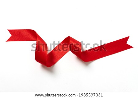 A roll red ribbon isolated on white background Royalty-Free Stock Photo #1935597031