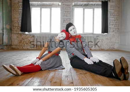 Male and female mime artists sitting on the floor