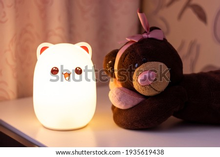 The baby cute bear-shaped night lamp with eyes and ears near a toy teddy bear with a bow on its head and a heart in its hands on the bedside table in the pink-style room glows in the dark