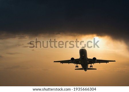 Plane goes on takeoff at sunset. Landing plane at sunset. Cloudy sky Royalty-Free Stock Photo #1935666304