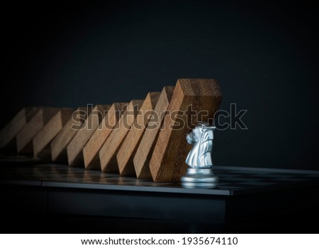 Crisis management, risk management, crisis solving or problem solving concept. Knight chess stopping wooden dominoes from collapsing on chessboard in black scene. Royalty-Free Stock Photo #1935674110