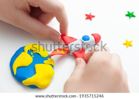 A young boy playing with a space rocket that is blasting off from the planet Earth to the stars. The space rocket and the planet Earth are made out of polymer clay. Shallow depth of field.