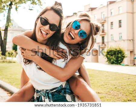 Two young beautiful smiling hipster female in trendy summer white t-shirt clothes.Sexy carefree women posing on street background. Model jumping on her friend back, gives piggyback riding outdoors Royalty-Free Stock Photo #1935731851