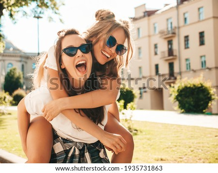Two young beautiful smiling hipster female in trendy summer white t-shirt clothes.Sexy carefree women posing on street background. Model jumping on her friend back, gives piggyback riding outdoors Royalty-Free Stock Photo #1935731863