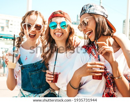 Three young beautiful smiling hipster female in trendy summer clothes.Sexy carefree women posing outdoors.Positive models holding and drinking fresh cocktail smoothie drink in plastic cup with straw Royalty-Free Stock Photo #1935731944