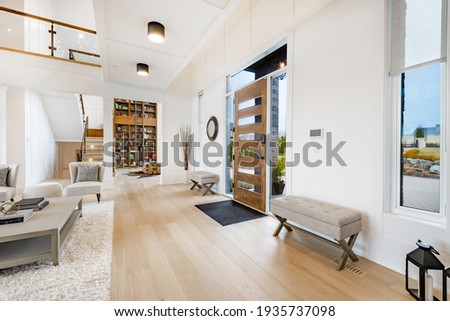 Large open concept great room with fireplace and wooden beams Royalty-Free Stock Photo #1935737098